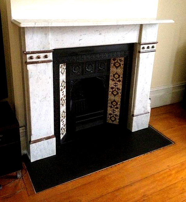 A restored Federation marble mantle with a honed granite hearth stone